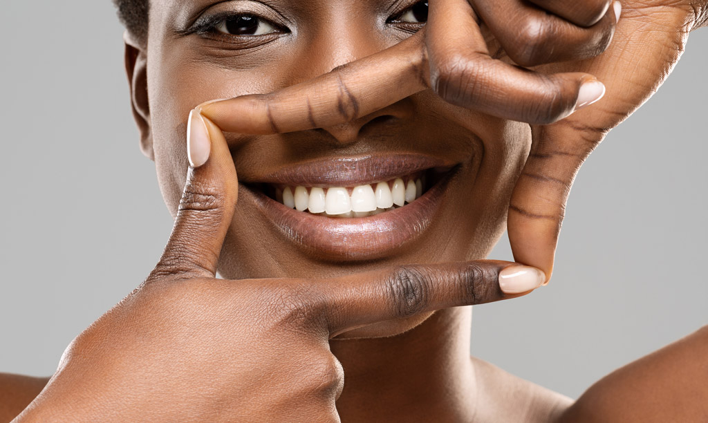 Beautiful black woman framing her healthy white teeth with fingers